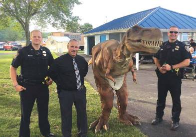 From left, Officer Orndorff, new Dubois, Pa., Police Chief Clark and Officer Peterson pose with a dinosaur at the annual Community Days event. Clark is hoping to continue growing the department as a community-oriented department. (Photo provided)