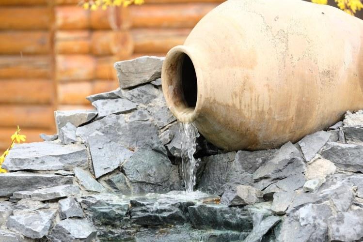 Decorative garden waterfall made with stone jar