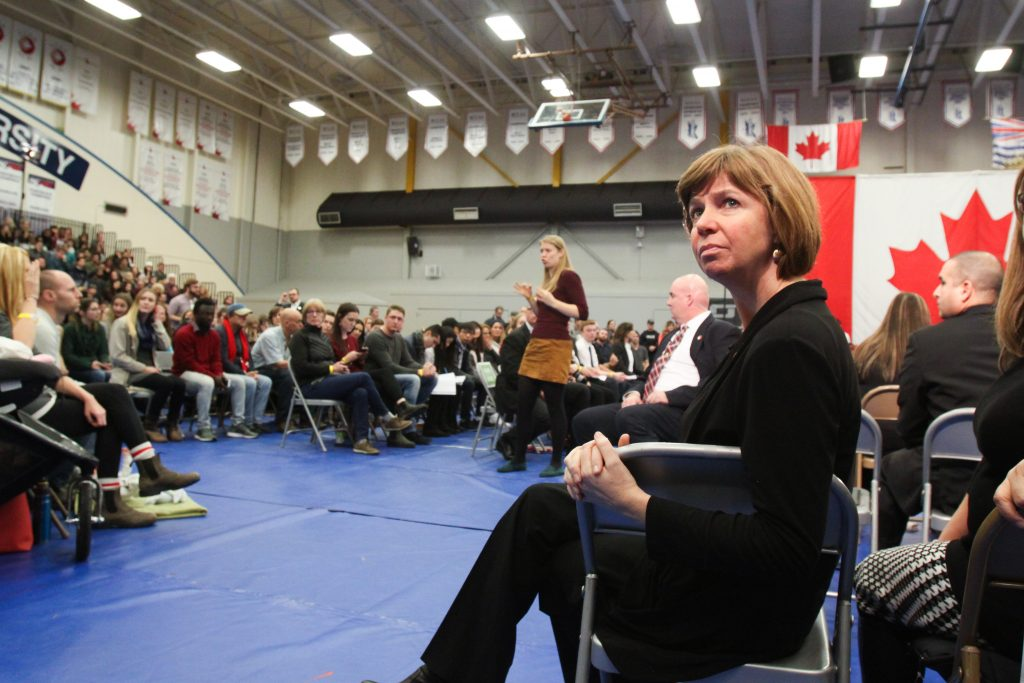 Sheila Malcolmson sits turned around in chair on right side of foreground, and out-of-focus crowd members are visible in background.