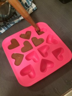 A pink heart stenciled ice cube tray is filled with chocolate fat bombs.