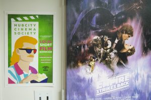Two distinct posters hang on the wall: one is the fifth episode of the Star Wars, The Empire Strikes Back; the other is a promotional poster of HCCS's Cinefest where a man with a ginger mullet eats popcorn while wearing 3D glasses