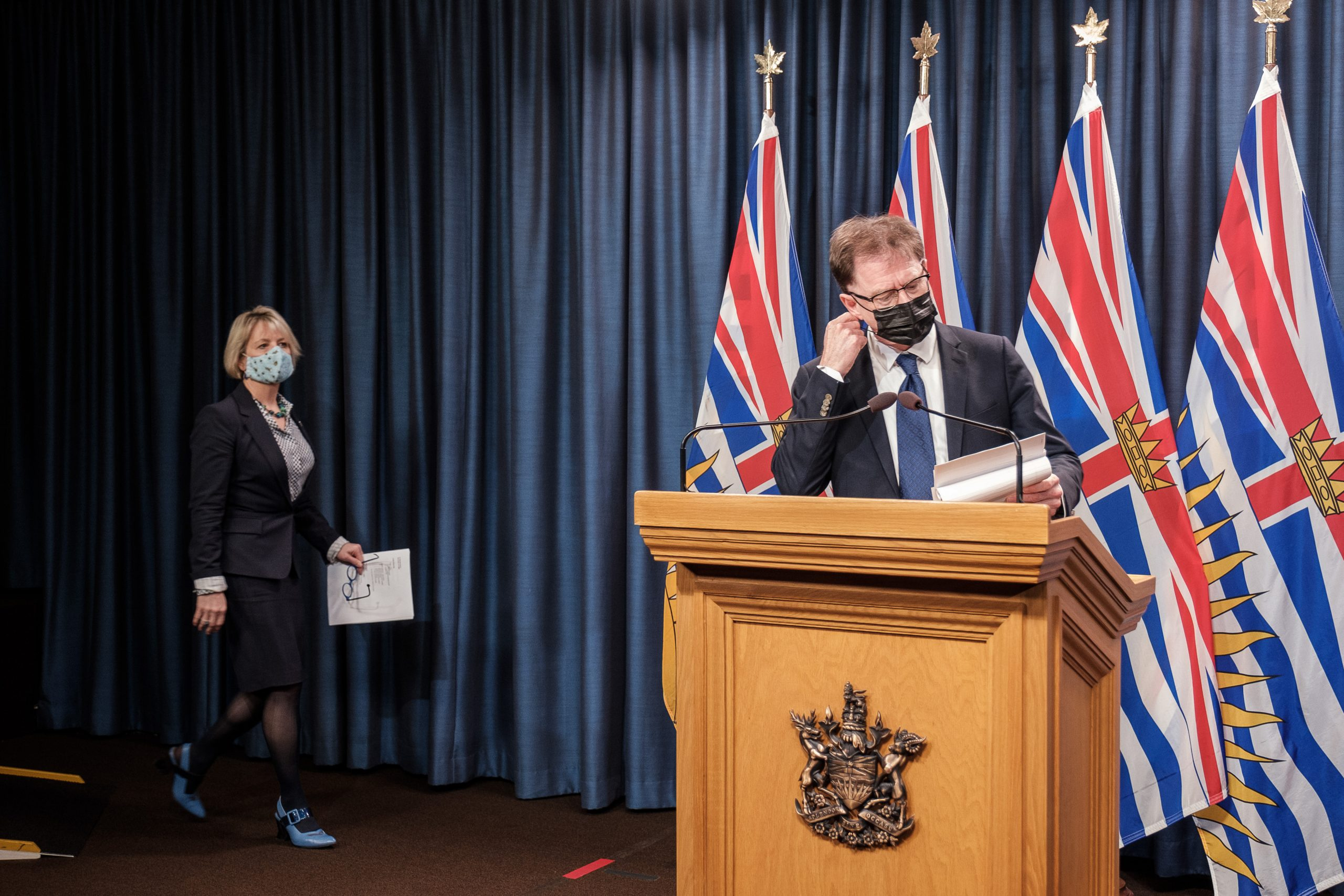 Adrian Dix stands at a podium as he starts to take off his black mask that is covering his face. Bonnie Henry walks towards the podium to the left as she wears a bright blue mask