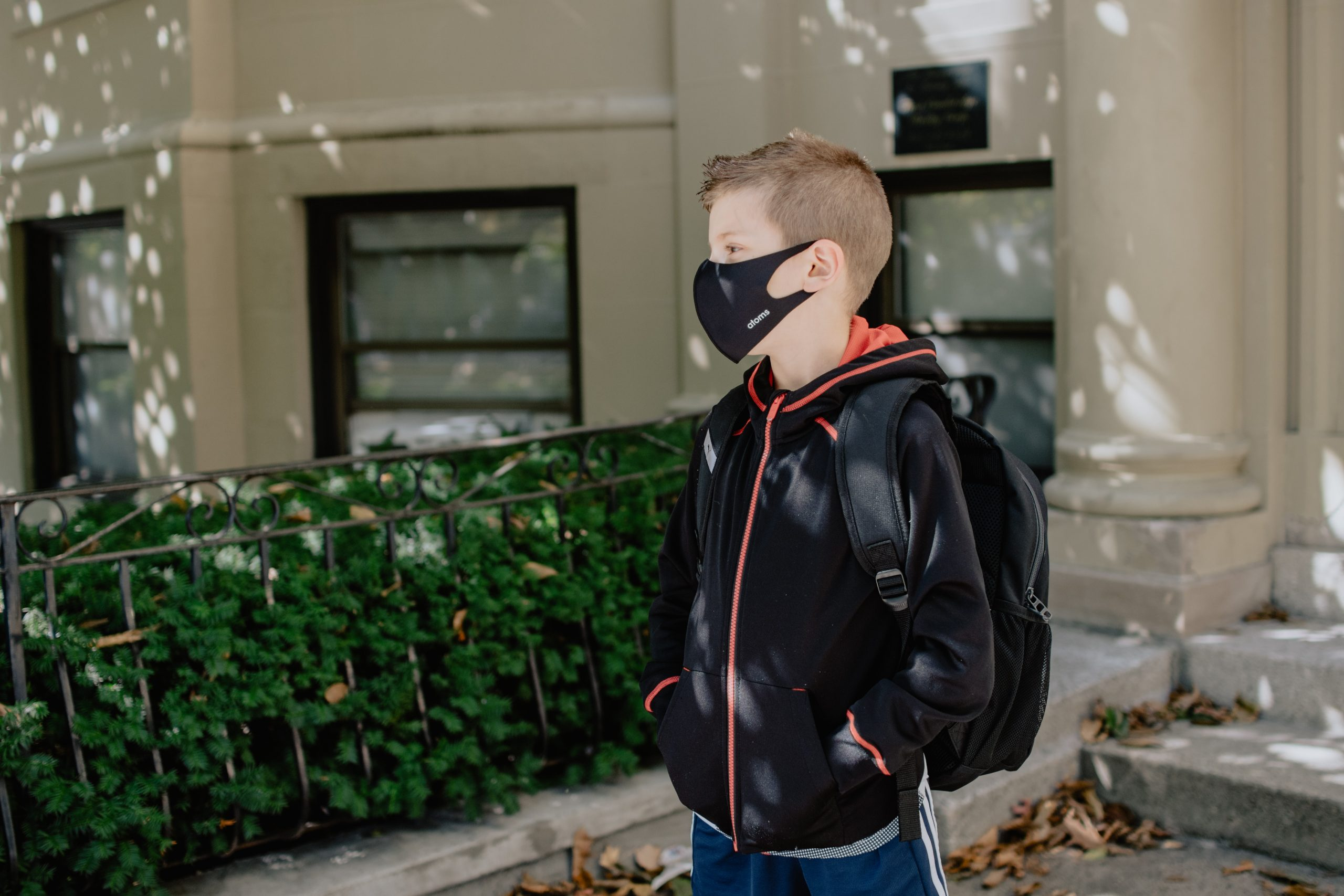 An elementary-age boy wearing a mask in front of a school.