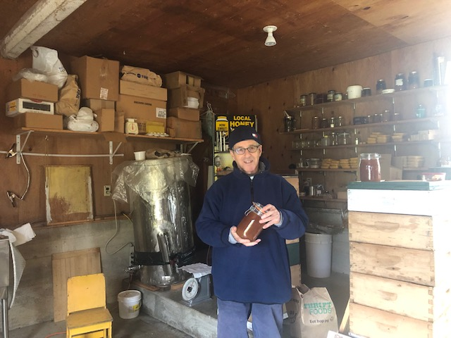 Sol stands in his honey shed where many wooden boxes and jars of honey line the walls