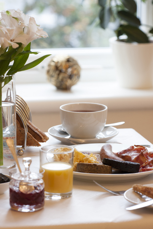 A close up image of a full cooked Scottish Breakfast at The Ness Guest House, Inverness, Scottish Highlands. Freshly cooked breakfast with sausage, bacon, black pudding and eggs, served with a teacup of tea and glass of fresh orange juice, toast and jam.
