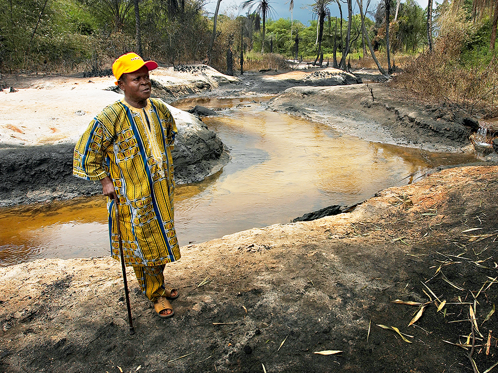 A Nigerian village chief looks at the site of a crude oil fire. Though rich in oil, Nigeria sits low on the Corruption Perceptions Index