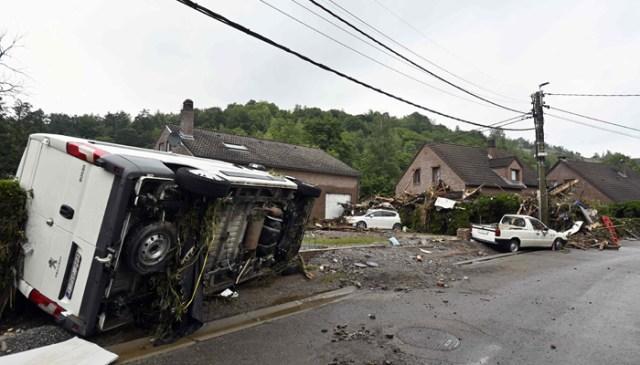 16 جولائی 2021 کو تروز میں حالیہ سیلاب سے تباہ ہونے والے علاقے میں الٹ گئی کاروں اور ملبے کے راستے میں سڑک۔ - اے ایف پی
