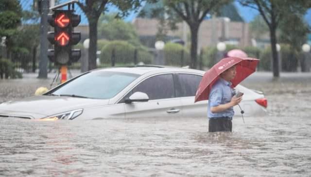 20 جولائی ، 2021 کو لی گئی اس تصویر میں دکھایا گیا ہے کہ چین کے وسطی صوبہ ہینان میں ژینگزہو میں موسلا دھار بارش کے بعد ایک شخص سیلاب کی گلی کے ساتھ ایک ڈوبی ہوئی کار سے گذر رہا ہے۔  - اے ایف پی / فائل