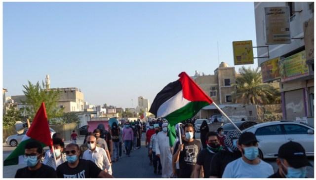 مظاہرین یکم اکتوبر 2021 کو بحرین کے دارالحکومت کے جنوب میں واقع سترا جزیرے میں اسرائیل مخالف ریلی کے دوران بحرینی اور فلسطینی جھنڈے اٹھا رہے ہیں۔