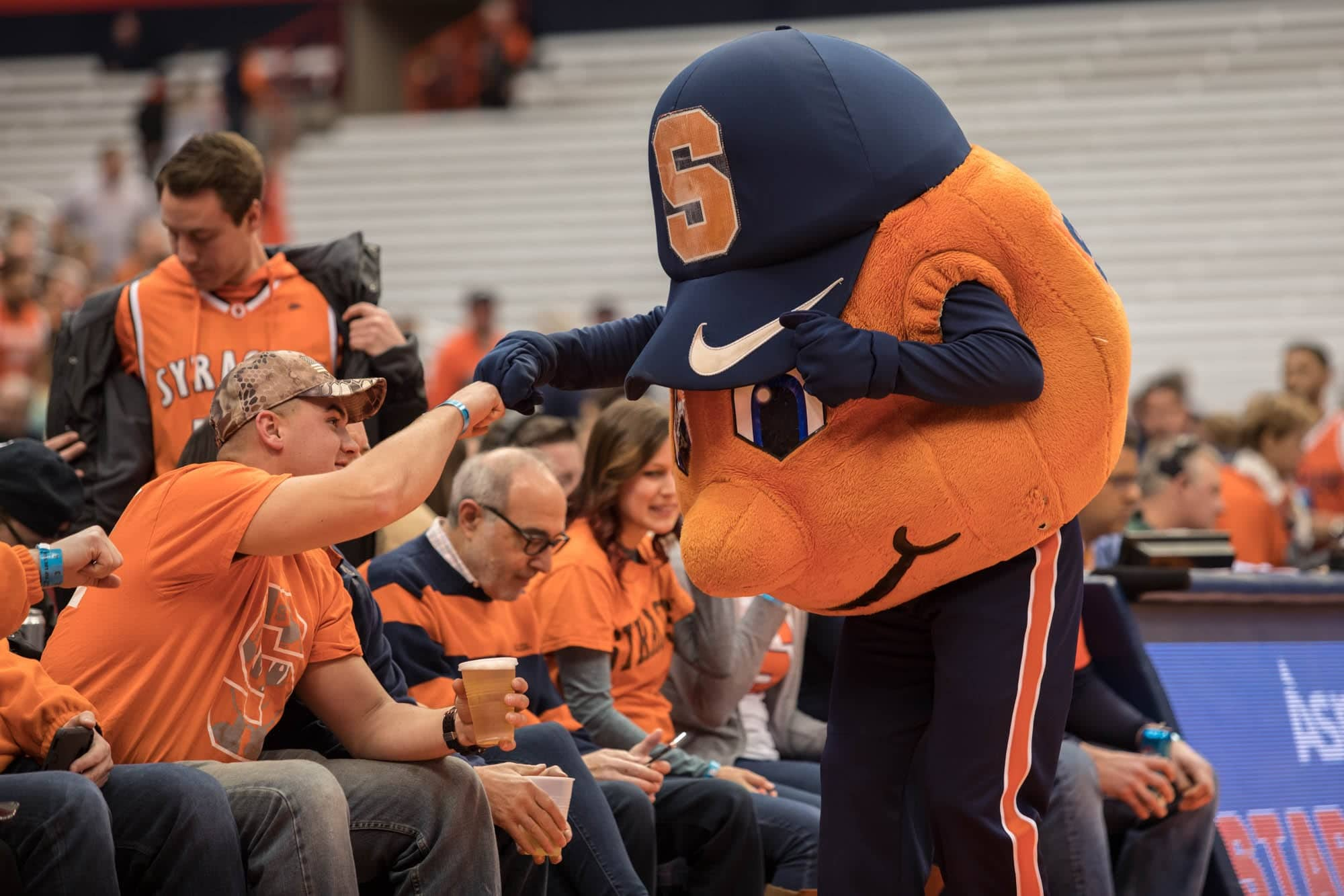 Otto the Orange fist bumps a fan