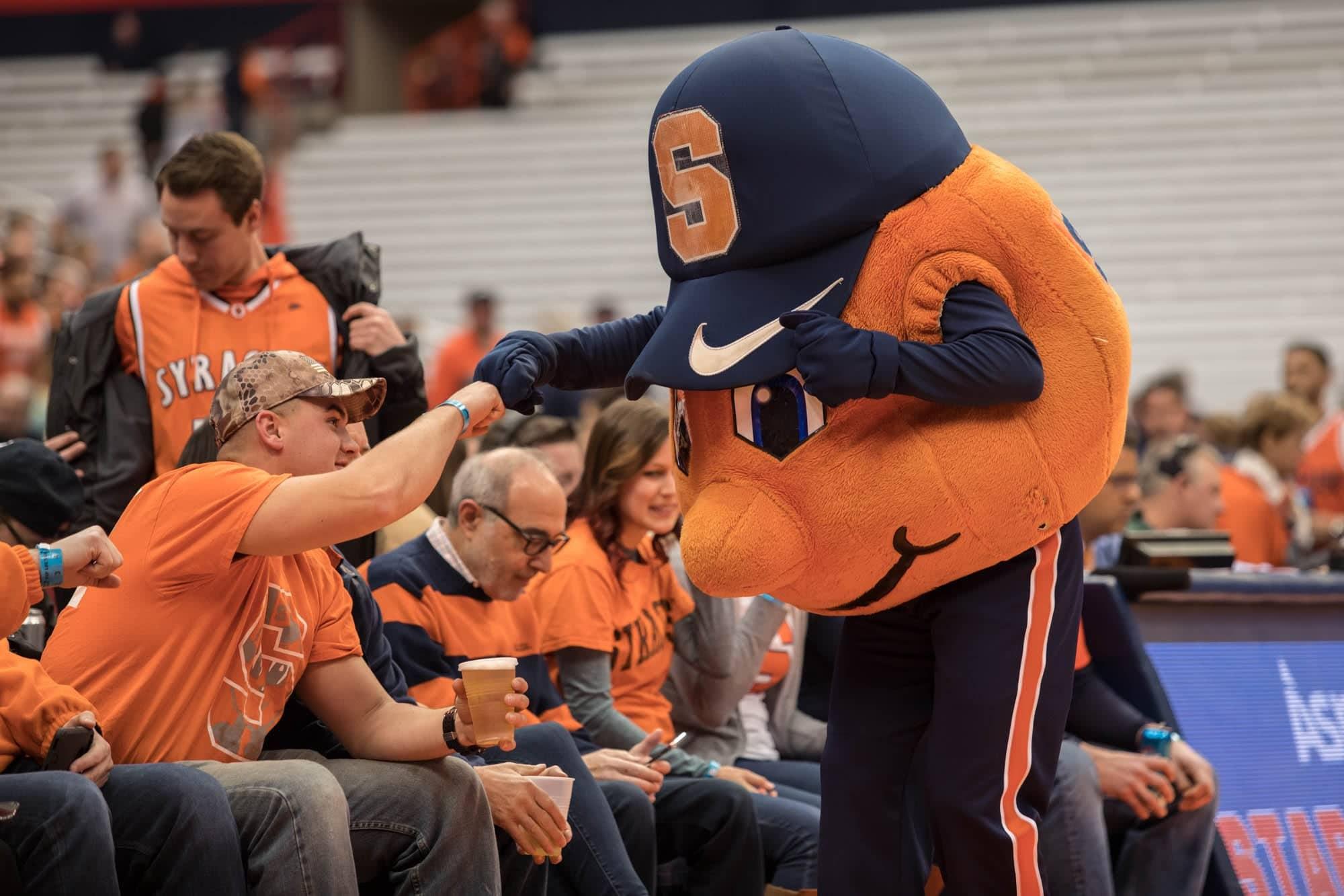 Otto the Orange fist bumps a fan