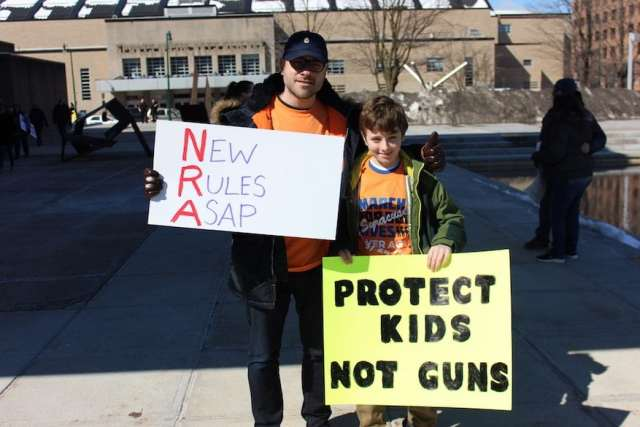 pair with signs at Syracuse march