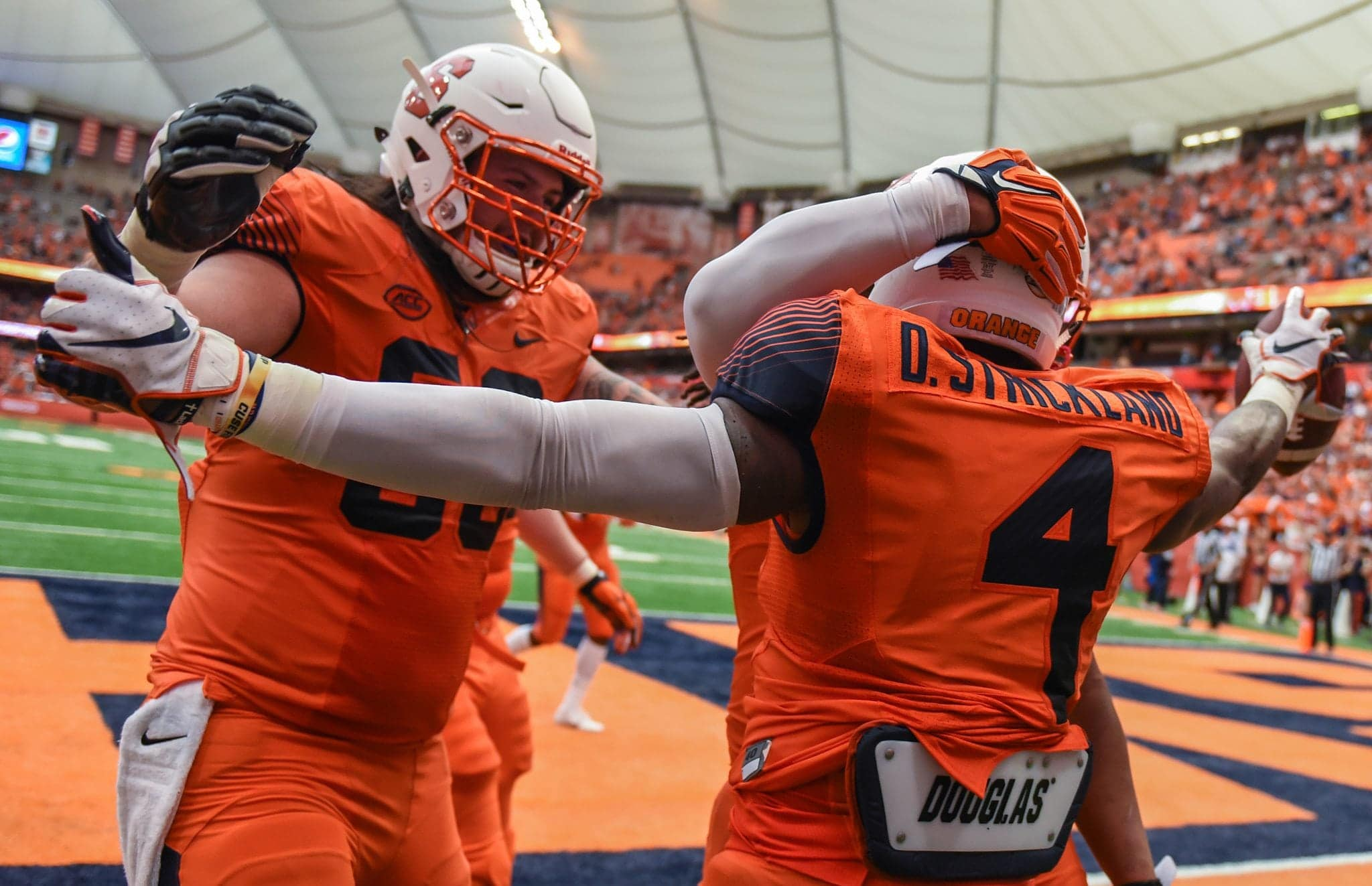 Syracuse University running back Dontae Strickland (4), celebrates a touchdown with his teammates.