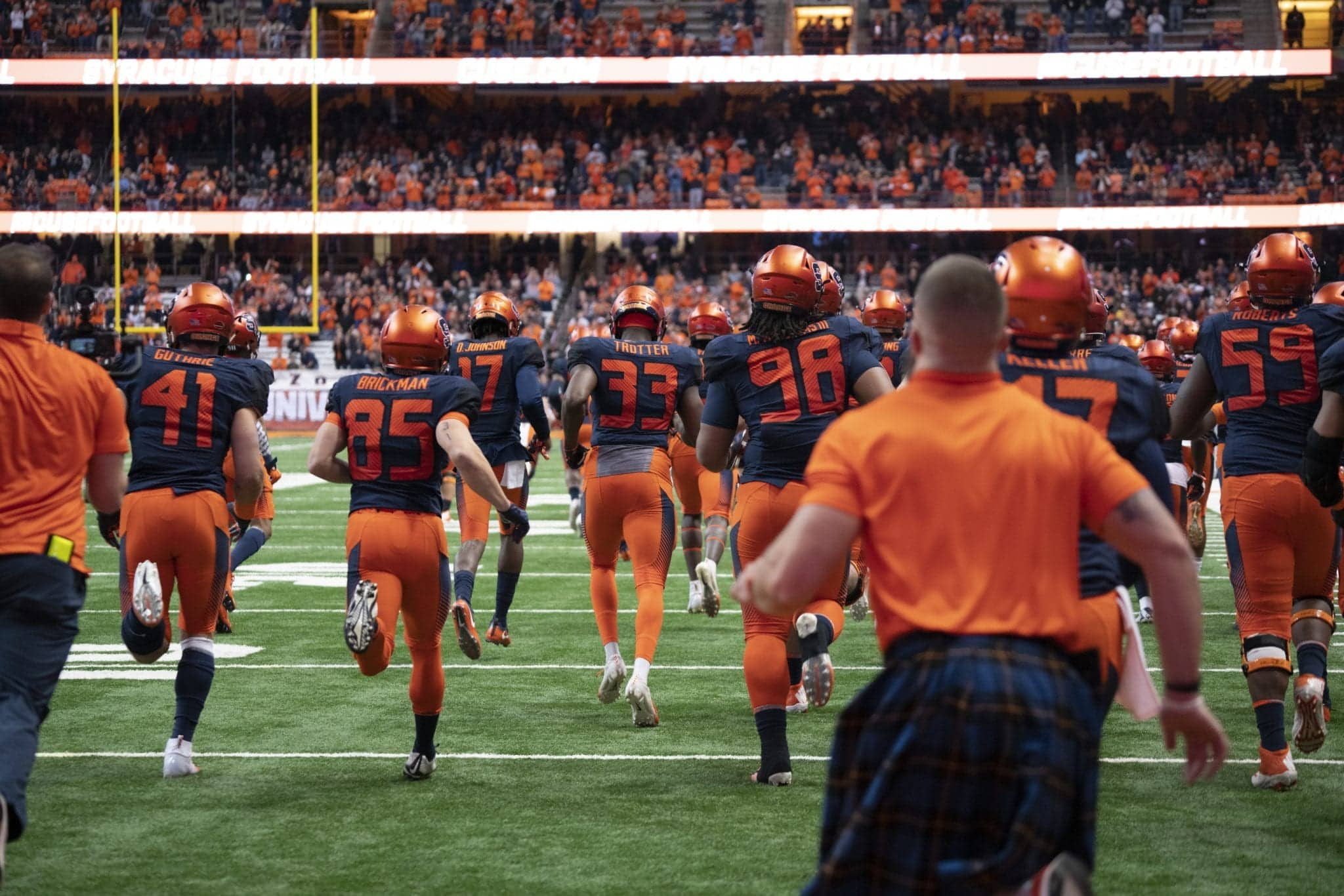 The Syracuse Orange football team runs onto field
