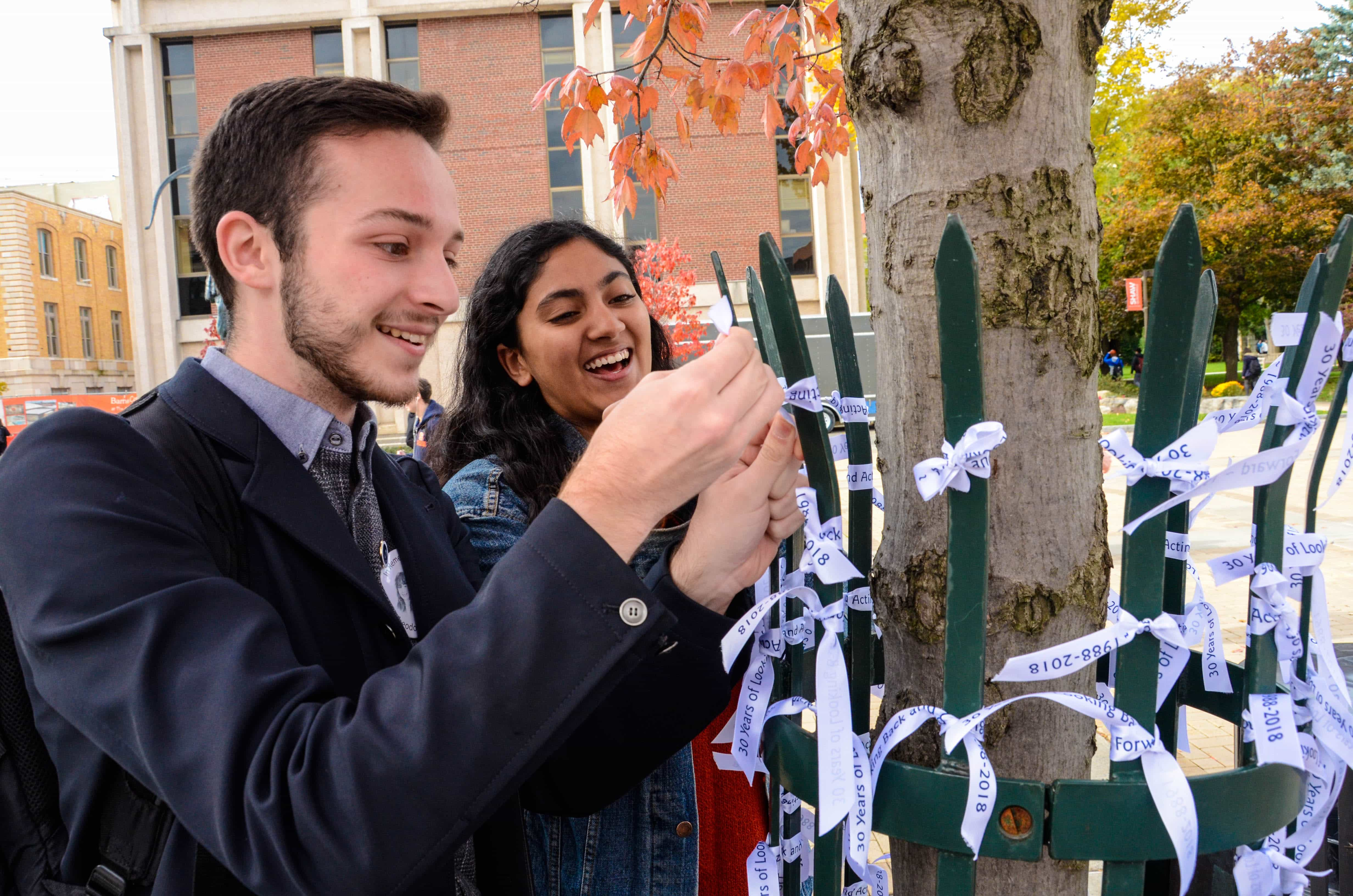 Senior David Robusto and sophomore Sameeha Saied tie their ribbons to a tree for Remembrance Week.