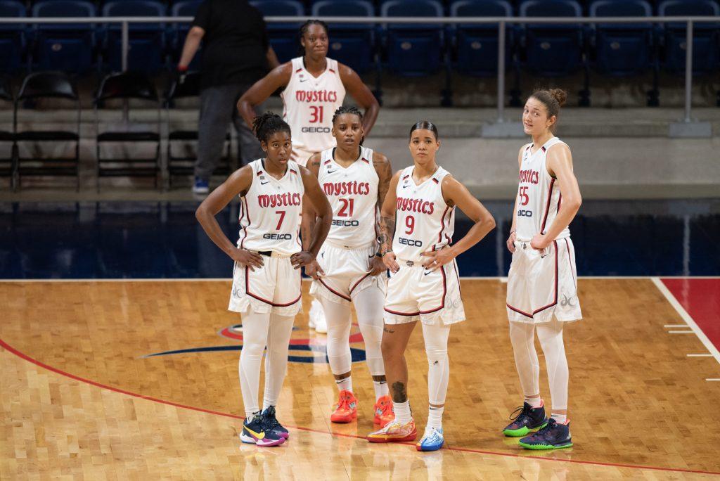 Washington Mystics players Ariel Atkins (7), Tina Charles (31), Shavonte Zellous (21), Natasha Cloud (9) and Theresa Plaisance (55) prepare to resume play during a game against the Phoenix Mercury on May 18, 2021. (Photo credit: Domenic Allegra)