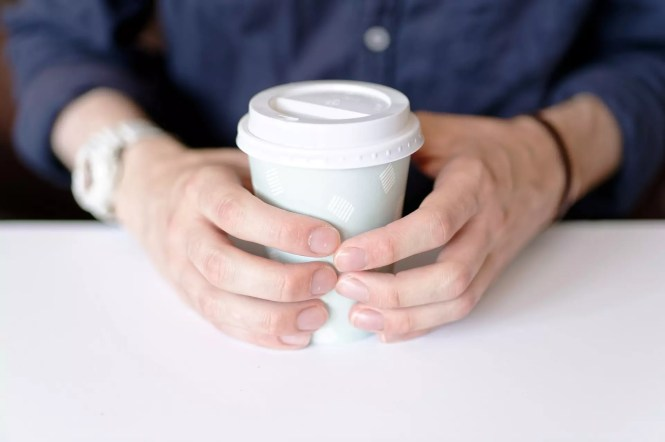 Man holding a cup of coffee with his hands