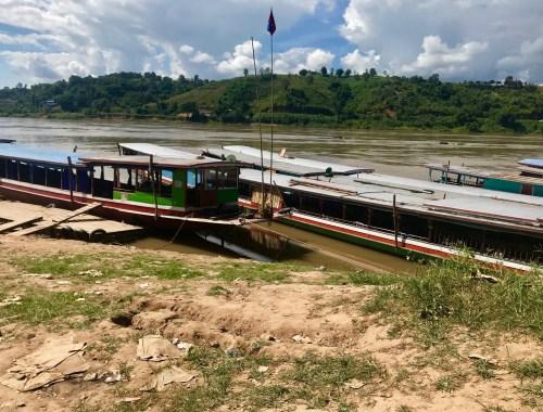 slow boats docked on mekong river