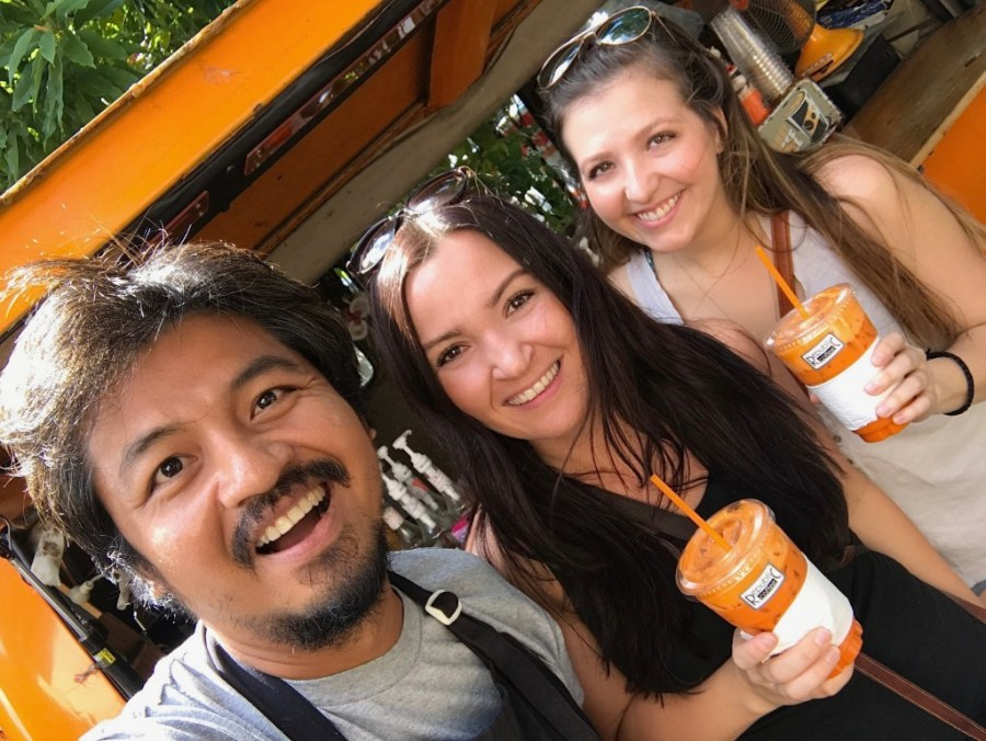 women posing with coffee shop owner