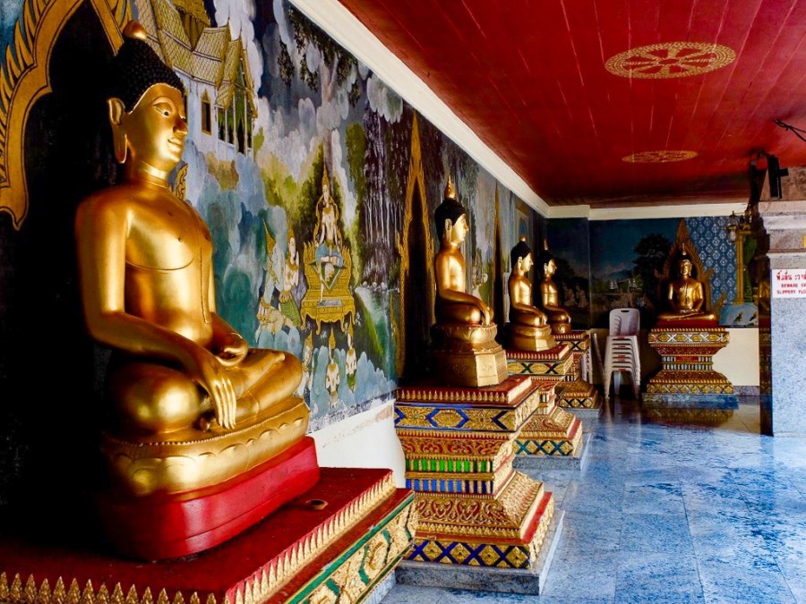 buddha statues line wall of temple