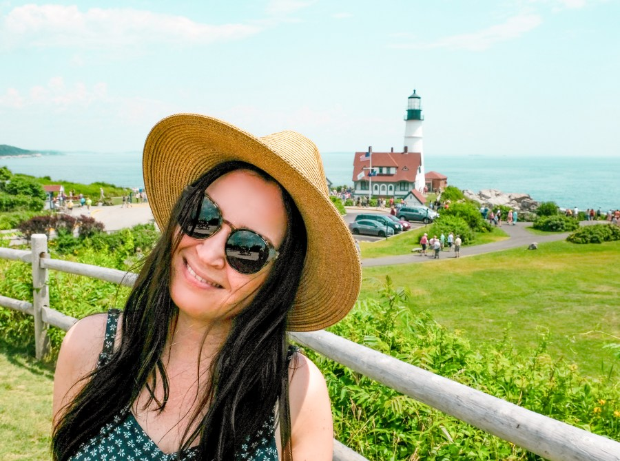 woman posing in front of Maine light house