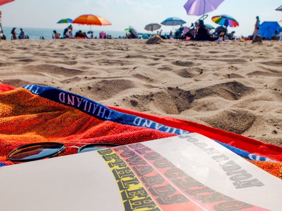 beach towel and book on sand