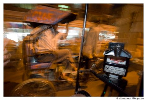 A bicycle rickshaw passes a petrol rickshaw at night in Jaipur, India