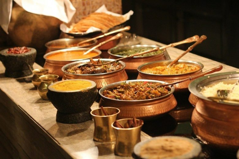 A buffet table at an India restaurant with many vegan Indian dishes