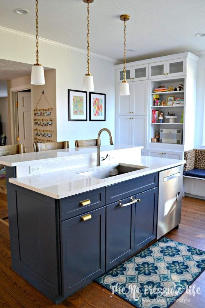 Navy blue kitchen island with white quartz counters and organized cleaning supplies under the kitchen sink.