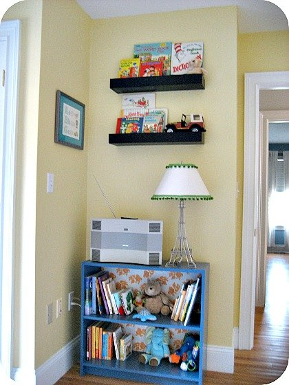 Nursery reading nook with DIY bookcase with decorative paper backing.