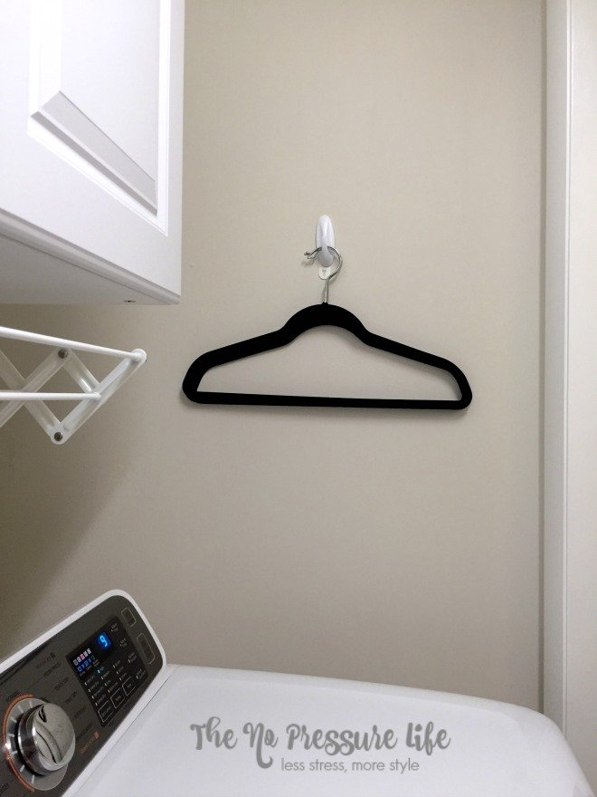 Quick laundry room organization tip: use a Command hook to hold extra hangers! Get more tips at The No Pressure Life.