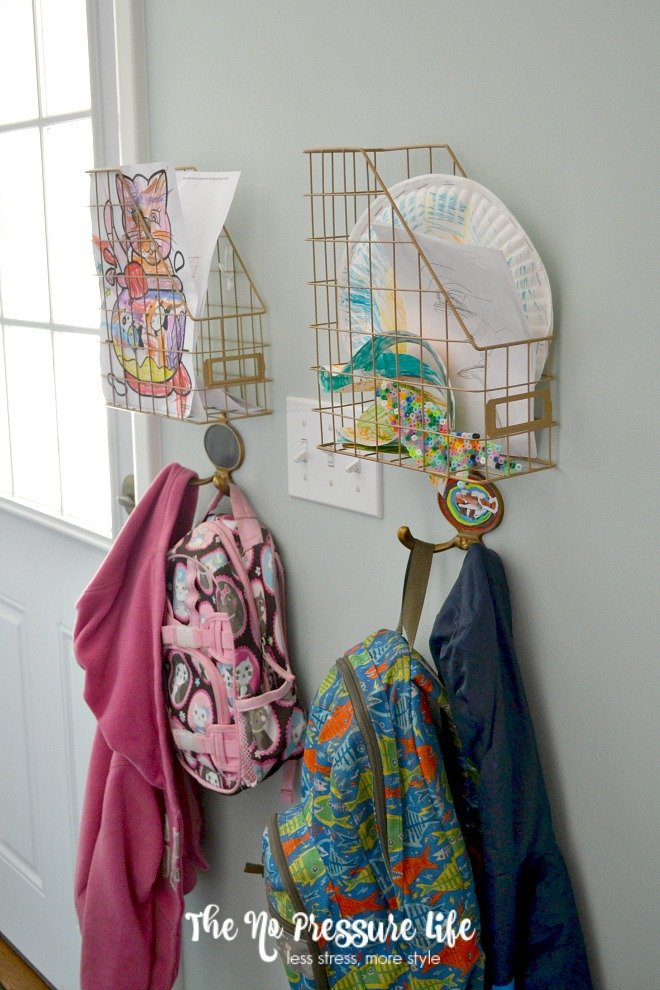 Organize kids paper with simple wall-mount cubbies made from magazine holders. Get more tips to stop paper clutter before it starts at The No Pressure Life.