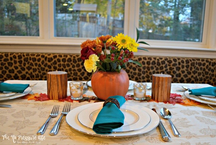Last-minute Thanksgiving centerpiece idea: pumpkin vase with mixed candles.