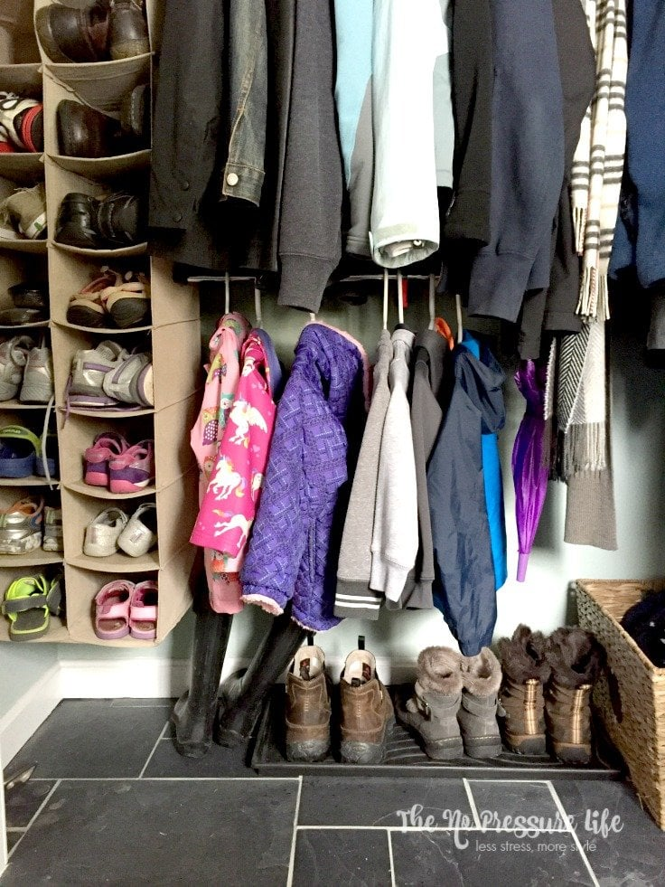 coat closet with a boot tray and hanging shoe organizer