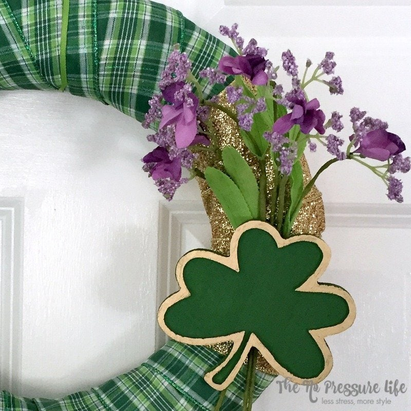 easy St. Patrick's Day wreath with green plaid ribbon and a shamrock on a door