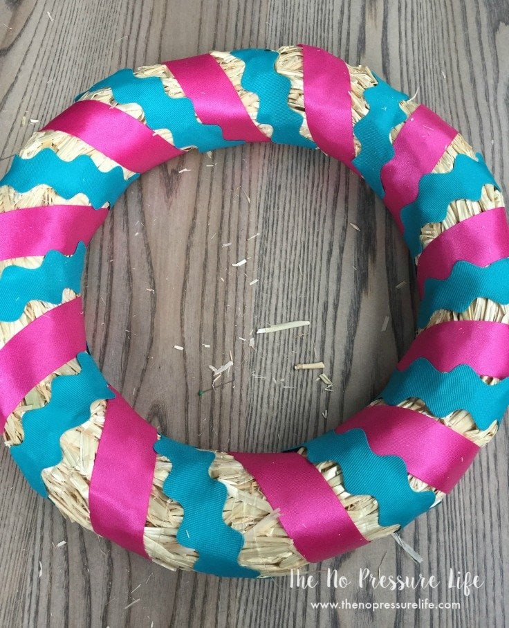 straw wreath wrapped in pink and blue ribbon - DIY Easter Wreath