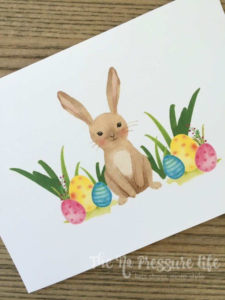 free spring printable art with a watercolor Easter bunny and colorful Easter eggs in grass.