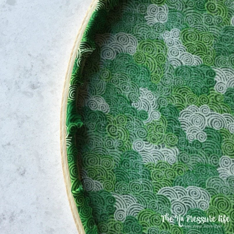 green fabric in an embroidery hoop for a shamrock craft