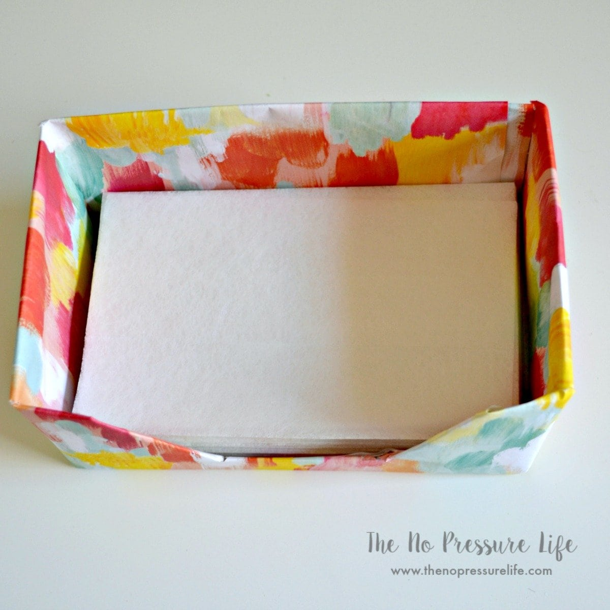 Smart! Cover a dryer sheet box in pretty wrapping paper and just refill it when empty. See more of this small laundry room makeover at The No Pressure Life.