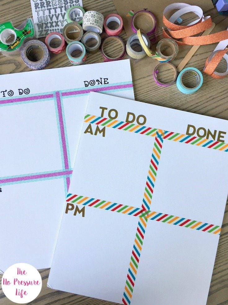 Two DIY chore charts for kids on a wood table with pile of colorful washi tape and letter stickers