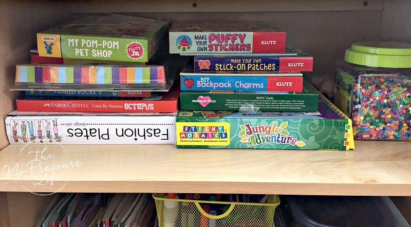 organized craft kits in a kitchen cabinet