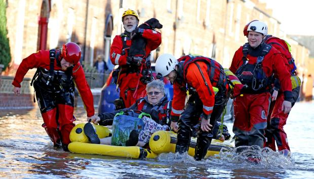 Rescue workers help a lady and her dog from the floods in Carlisle, Cumbria. Picture: Peter Byrne/PA Wire