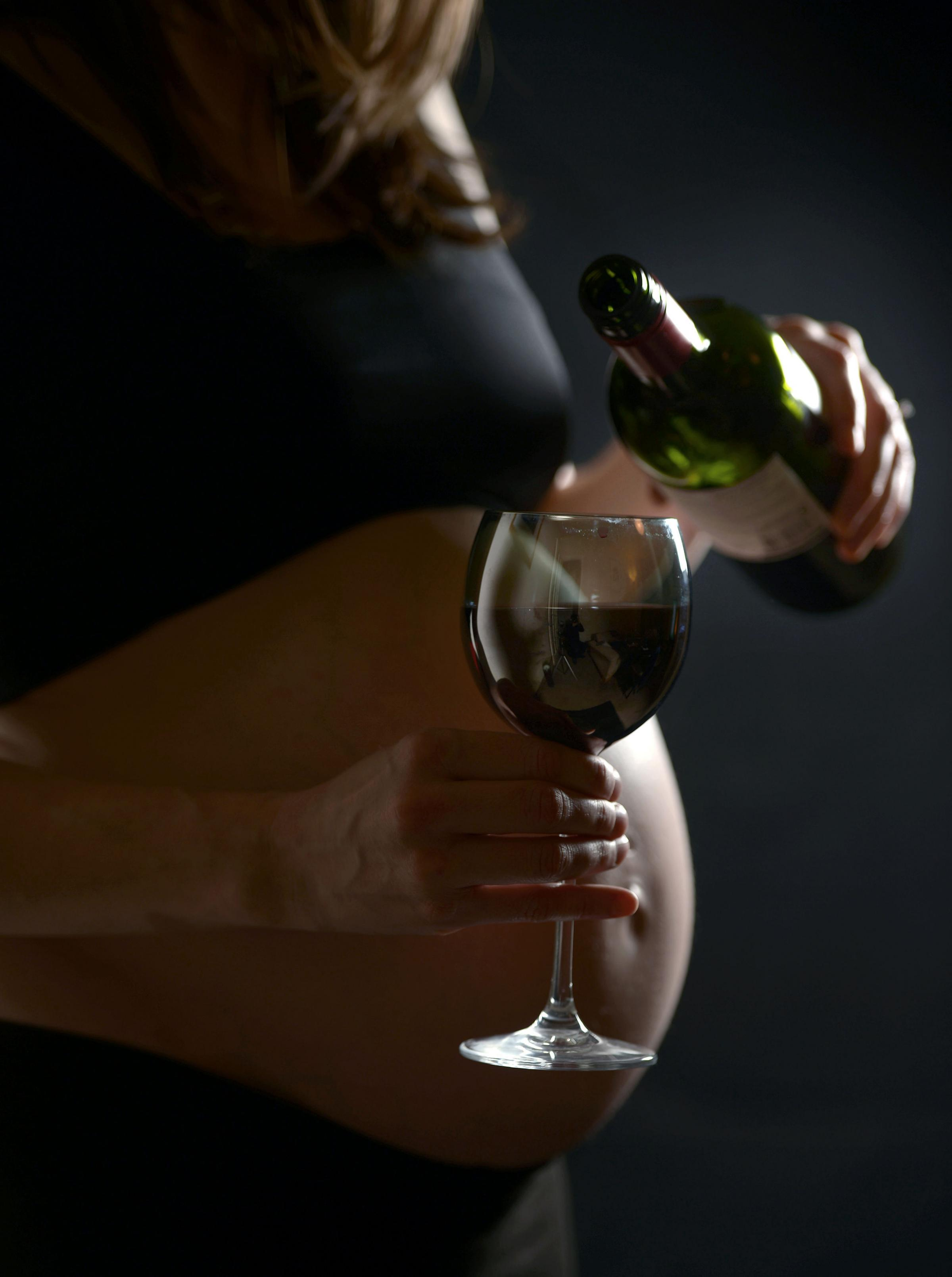 A pregnant woman with a glass of wine.