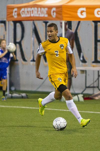 NKU men's soccer player, Alwin Komolong, dribble down the field during the match vs University of Cincinnati that finished in a tie. NKU hosted University of Cincinnati on Friday, August 29, 2014 at the NKU Soccer Stadium, drawing a tie at 1-1.