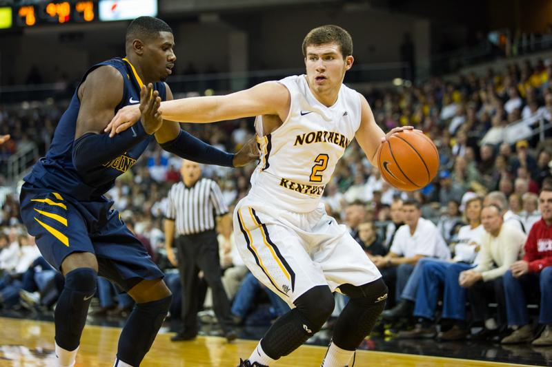 NKU+guard+Tayler+Persons+dribbles+the+ball+while+holding+off+a+West+Virginia+University+defender+during+NKU%27s+loss+to+WVU.