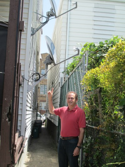 Photo by Ron Leir Len Rosenberg points to unwanted satellite TV equipment attached to his property.