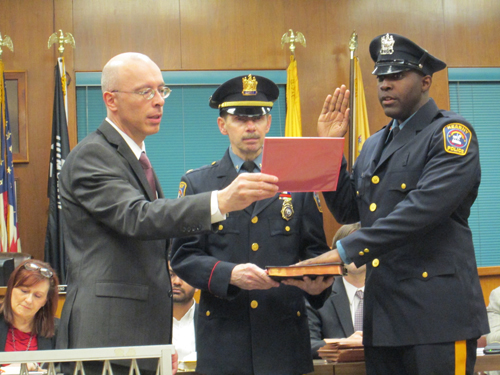 Photo by Ron Leir Jordenson Jean is sworn in by Mayor Alberto Santos as new member of the Police Department as Police Chief John Dowie assists with Bible.