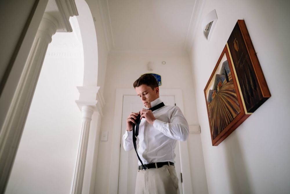 Groom learning how to tie a tie