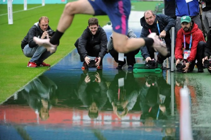Photographers capture a player as he jumps over, rather than runs through a puddle of water into the field ahead of South Africa's captain's run pre their semi-final against Wales. Image: Fotosport/David Gibson