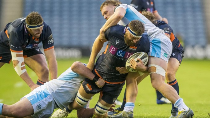 Nick Haining of Edinburgh is stopped in his tracks by two Glasgow Warriors players during last night's clash at Murrayfield. Image: ©Craig Watson